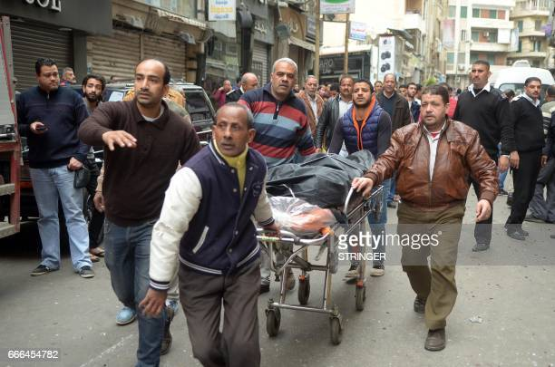 Egyptians wheel away a body near a church in Alexandria after a bomb blast struck worshippers gathering to celebrate Palm Sunday on April 9 2017 The...