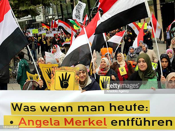 Egyptians with the 'Rabia sign' hold banners and wave national flags during ananti coup protest on October 62013 in Frankfurt Germany A group of more...