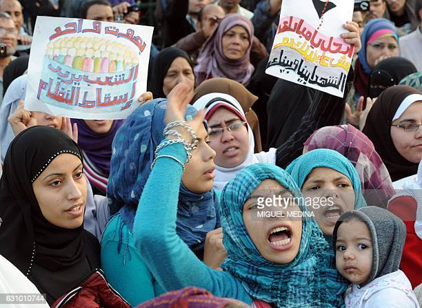 Egyptians women shout slogans and hold up signs reading in Arabic 'with one voice the nation wants the regime out' during a demonstration on February...