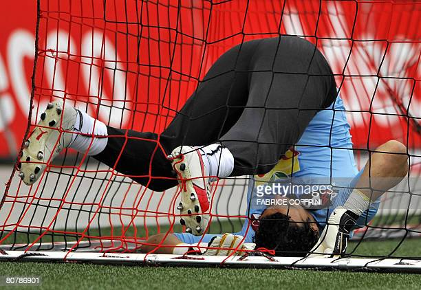 Egypt's African Nations Cup winning goalkeeper Essam ElHadary falls in the cage after receiving a goal during his first ever football game of the...