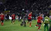 Egypt's AlAhly football players run away from clashes between rival football fans after their football match against AlMasry in Port Said on February...