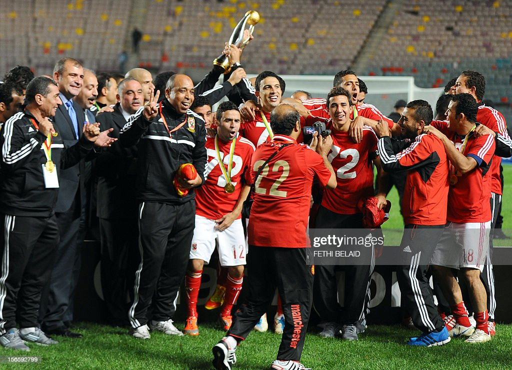 Egypt's al-Ahly team pass around the trophy as they celebrate after winning 2-1 against Esperance de Tunis in their CAF Confederation Cup football final at Rades Olympic stadium near Tunis, on November 17, 2012.