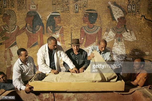 Egypt's antiquities chief Zahi Hawass supervises the removal of the linenwrapped mummy of King Tutankhamun from his stone sarcophagus in his...