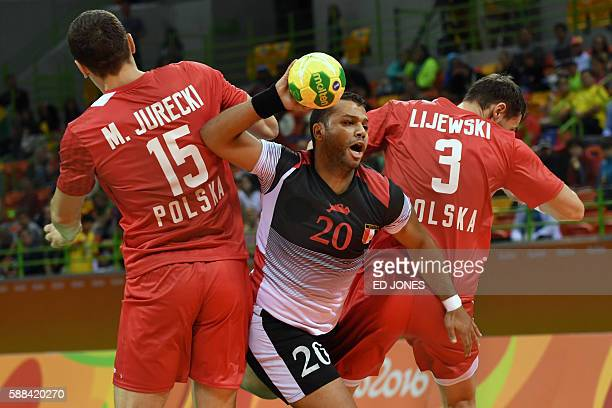 Egypt's centre back Mohamed Hashem gets past Poland's left back Michal Jurecki and Poland's right back Krzysztof Lijewski during the men's...