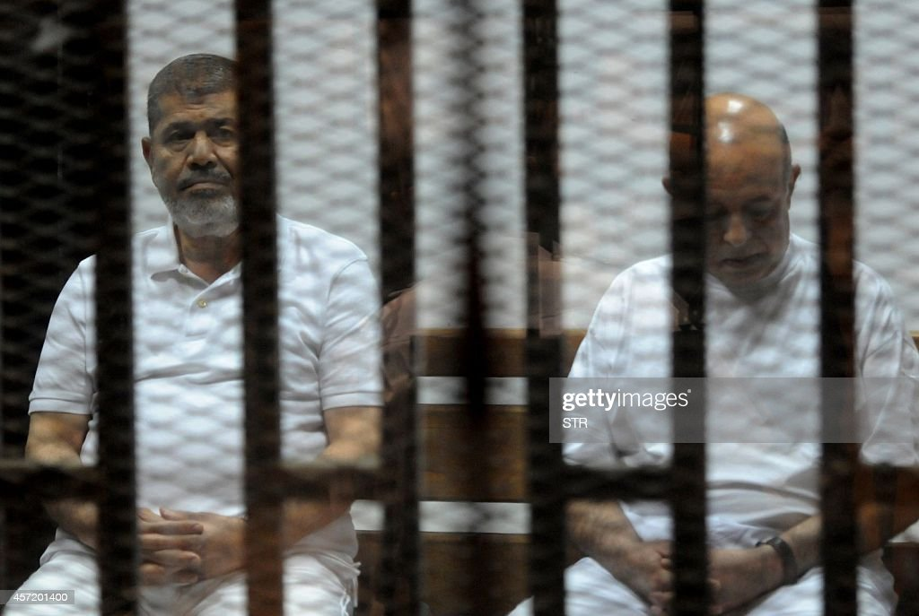 Egypt's deposed Islamist president <a gi-track='captionPersonalityLinkClicked' href=/galleries/search?phrase=Mohamed+Morsi&family=editorial&specificpeople=7484676 ng-click='$event.stopPropagation()'>Mohamed Morsi</a> (L) and former presidential chief of staff Rafaa el-Tahtawi, sit inside the defendants cage during his trial at the police academy in Cairo on October 14, 2014. Morsi is on trial in several cases and faces a death sentence if convicted of espionage and terrorism related charges.