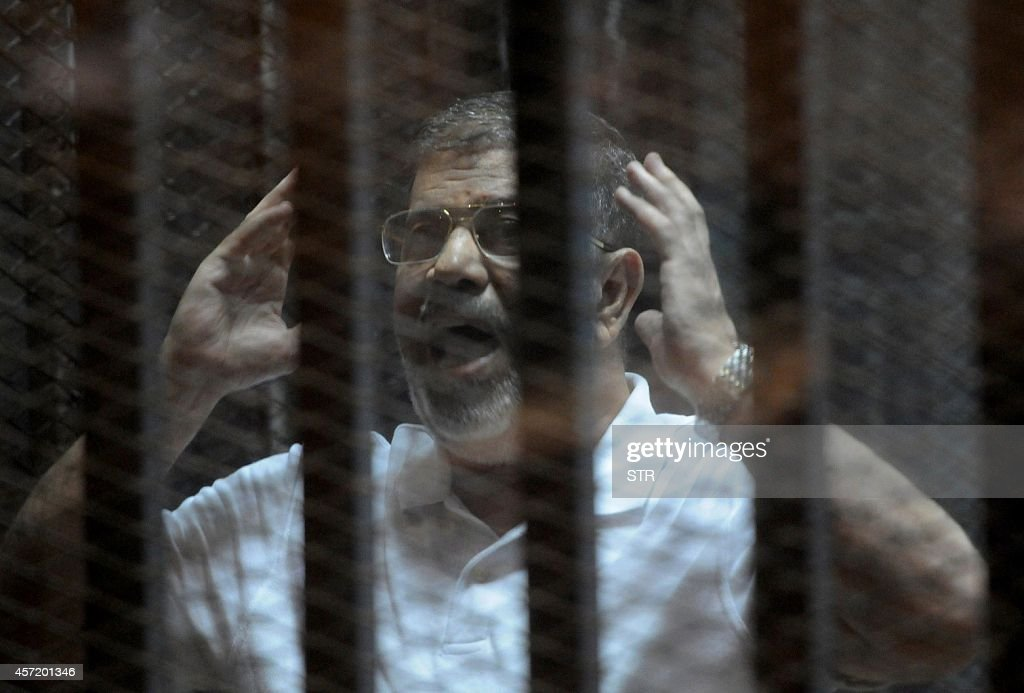 Egypt's deposed Islamist president <a gi-track='captionPersonalityLinkClicked' href=/galleries/search?phrase=Mohamed+Morsi&family=editorial&specificpeople=7484676 ng-click='$event.stopPropagation()'>Mohamed Morsi</a> gestures inside the defendants cage during his trial at the police academy in Cairo on October 14, 2014. Morsi is on trial in several cases and faces a death sentence if convicted of espionage and terrorism related charges.