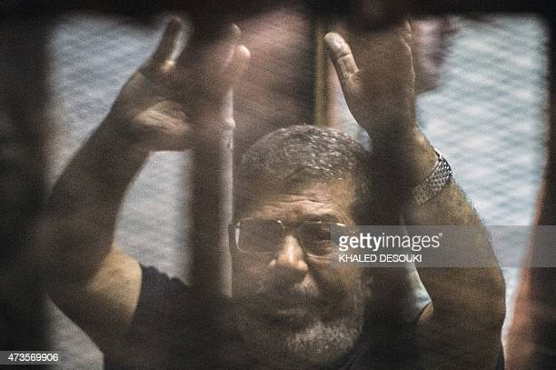 Egypt's deposed Islamist president Mohamed Morsi raises his hands from behind the defendant's cage as the judge reads out his verdict sentencing him...