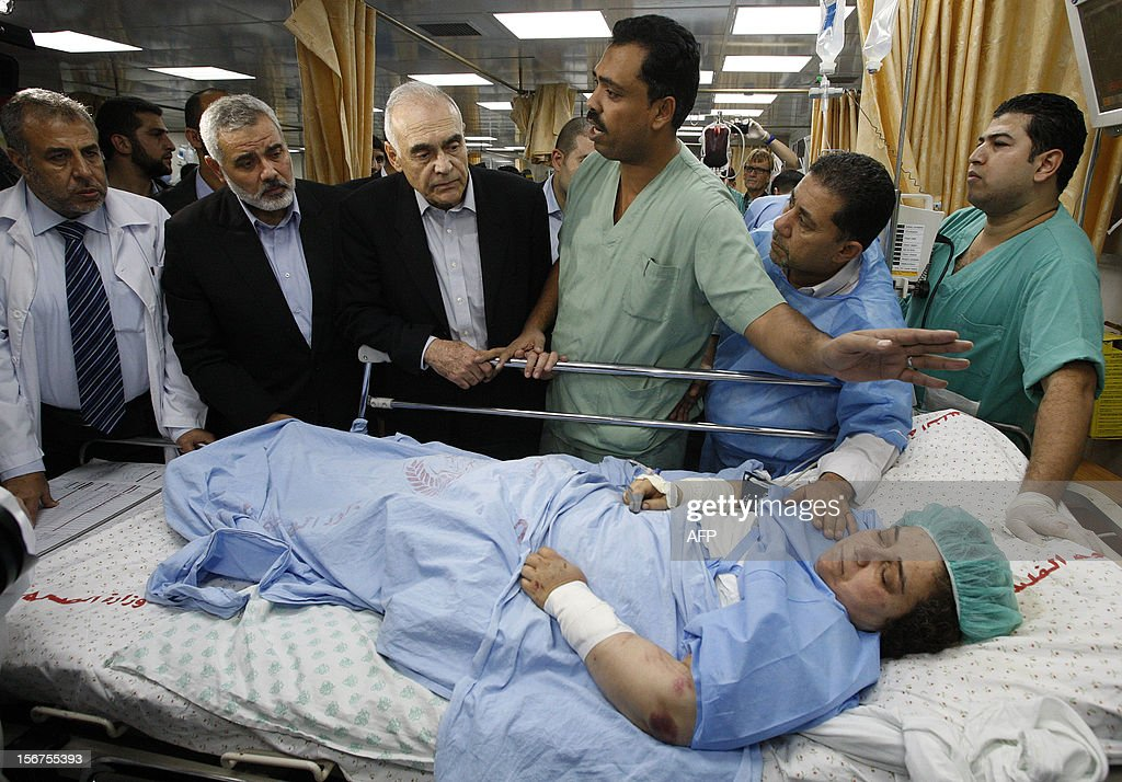 Egypt's Foreign Minister Mohamed Kamel Amr (3rd L) and senior Hamas leader Ismail Haniya (2nd L) look at a Palestinian woman, who according to Palestinian medics was wounded in an Israeli air strike, at a hospital in Gaza City on November 20, 2012. A top delegation of Arab ministers led by al-Arabi began a solidarity mission in Gaza as an Israeli air offensive entered its seventh day. AFP PHOTO/POOL/Ahmed Zakot