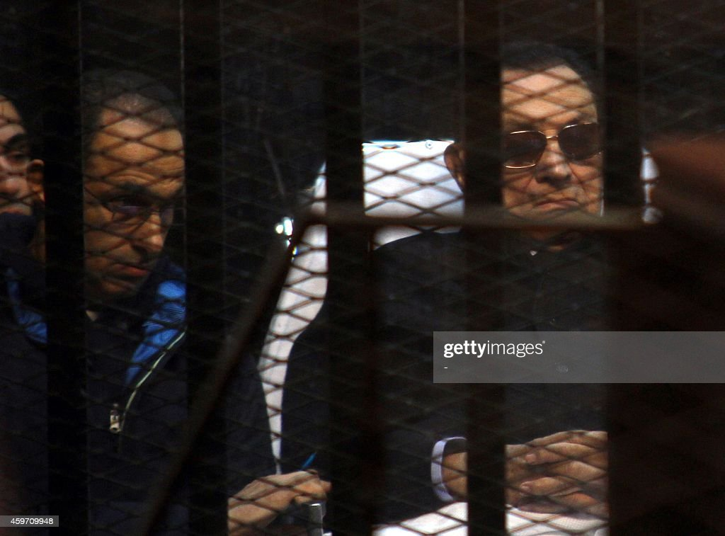 Egypt's former president <a gi-track='captionPersonalityLinkClicked' href=/galleries/search?phrase=Hosni+Mubarak&family=editorial&specificpeople=201752 ng-click='$event.stopPropagation()'>Hosni Mubarak</a> (R) and his son Gamal sit behind bars during a court hearing on November 29, 2014 in the capital Cairo. The court acquitted all seven security commanders charged with murder alongside ousted president <a gi-track='captionPersonalityLinkClicked' href=/galleries/search?phrase=Hosni+Mubarak&family=editorial&specificpeople=201752 ng-click='$event.stopPropagation()'>Hosni Mubarak</a> over the deaths of protesters during a 2011 uprising. AFP PHOTO / STR