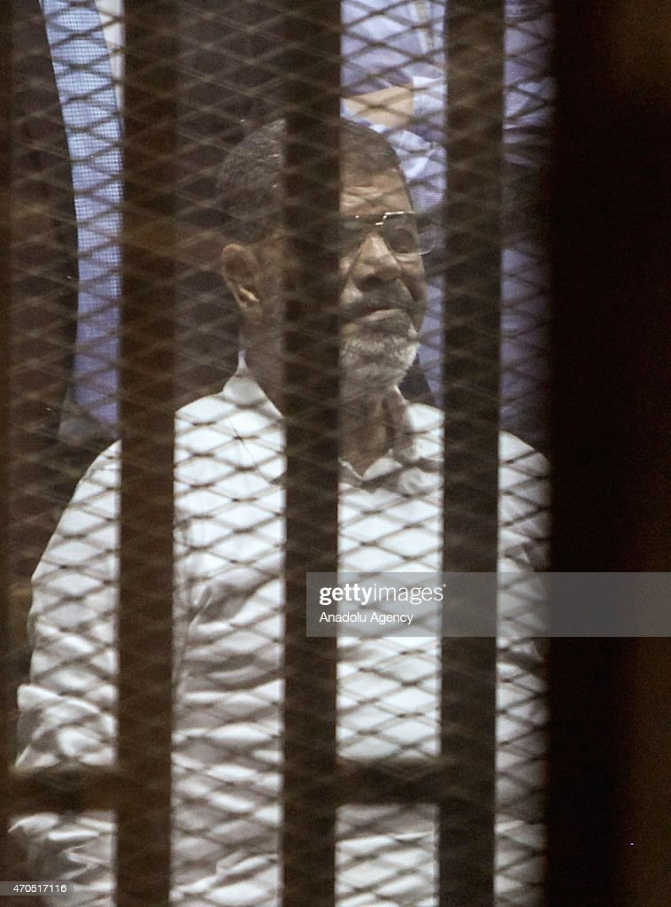 Egypt's former president Mohammed Morsi looks from behind dock bars during trial session, in Cairo, Egypt on 21 April 2015. An Egyptian court sentenced Mohammed Morsi to 20 years in prison over the killing of protesters during a 2012 demonstration outside the presidential palace in Cairo.