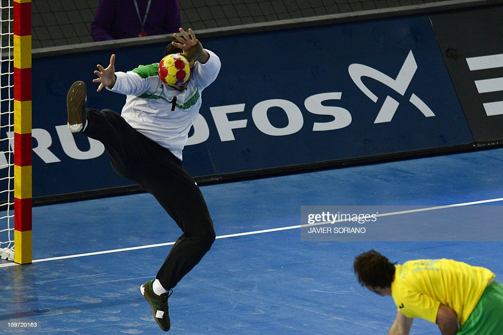 Egypt's goalkeeper Karim Mostafa (L) stops a shot by Australia's pivot Tommy Fletcher during the 23rd Men's Handball World Championships preliminary round Group D match Egypt vs Australia at the Caja Magica in Madrid on January 19, 2013. AFP PHOTO/ JAVIER SORIANO