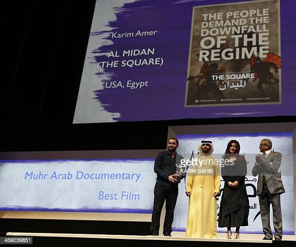 Egypt's Karim Amer is presented by Sheikh Mansour son of Dubai ruler Sheikh Mohammed bin Rashid alMaktoum with the award of Muhr Arab Documentary...