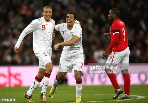Egypt's Mohamed Zidan celebrates with team mate Ahmed Fathi after scoring his side's first goal of the game as England's Jermain Defoe looks on