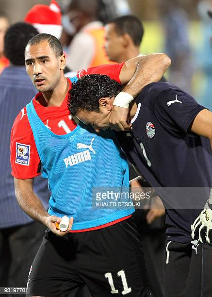 Egypt's Mohammed Shawki comforts goalkeeper Essam alHadary after losing the 2010 World Cup qualifying playoff football match against Algeria in...