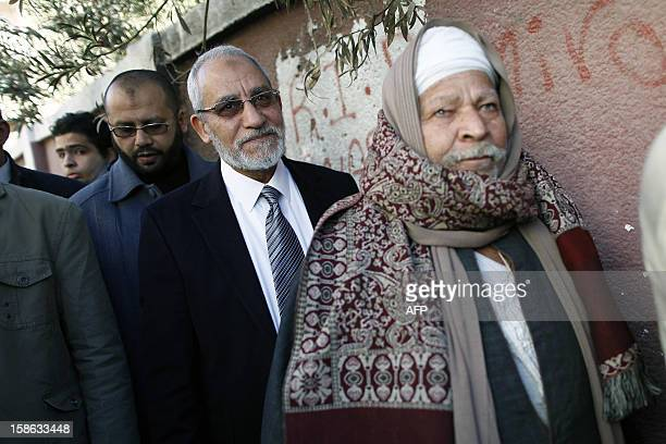 Egypt's Muslim Brotherhood leader Mohammed Badie queues with other voters at a polling station during the second round of a referendum on a new draft...