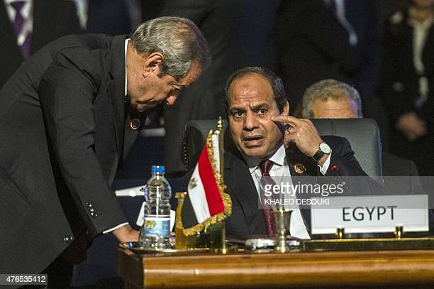 Egypt's President Abdel Fattah alSisi talks to his Minister of Industry and Trade Mounir Fakhry Abdel Nour during the closing session of an African...