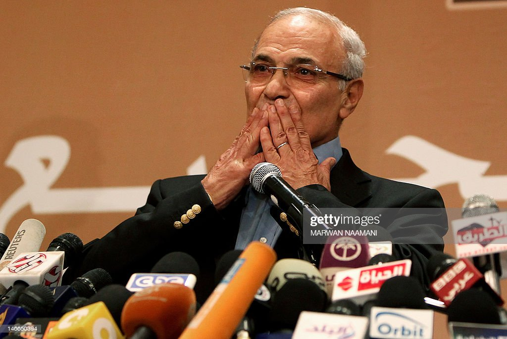 Egypt's presidential candidate Ahmed Shafiq, the last premier of ousted Egyptian strongman Hosni Mubarak, greets supporters during a press conference in Cairo, on June 21, 2012. Egypt on Thursday braced for a showdown between the military and the Muslim Brotherhood as the electoral commission delayed announcing the winner of a presidential poll claimed by the Islamists. A delay in announcing the results from the run-off, which had been due on Thursday, heightened fears of a 'soft coup' by the ruling military, which has already disbanded the Islamist-led parliament and granted itself sweeping powers. AFP PHOTO/MARWAN NAAMANI