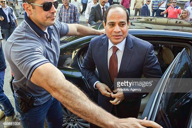 Egypt's resigned defense minister AbdelFattah alSisi one of the only two presidential contenders arrives at a polling station to cast his vote in...