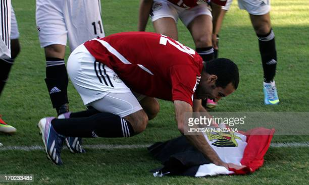 Egypt's striker Aboutrika Salaire holds an Egyptian flag as he celebrates with teammates at the end of a 2014 World Cup qualifying football match...