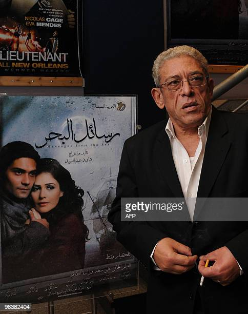 Egypt's veteran director Dawud Abdel Sayyed poses in front of a poster at a movie theatre in Cairo on February 3 advertising his latest film 'Rasayel...