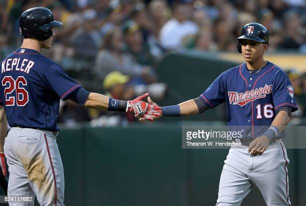 Ehire Adrianza of the Minnesota Twins is congratulated by Max Kepler after Adrianza scored against the Oakland Athletics in the top of the fourth...