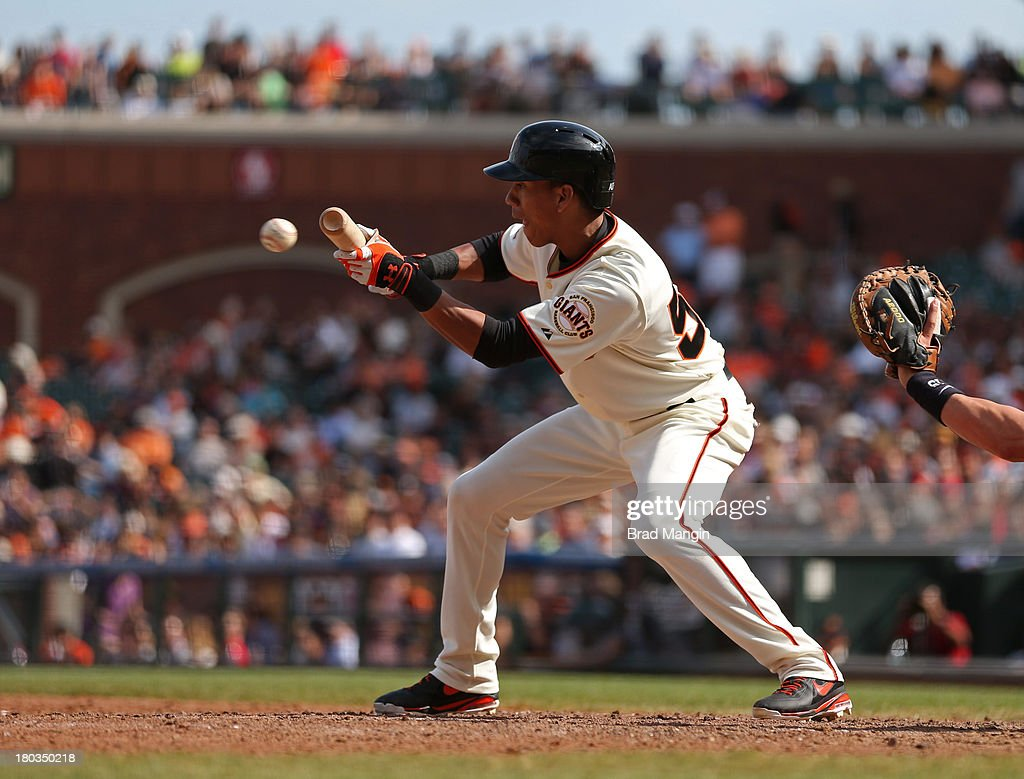 Ehire Adrianza of the San Francisco Giants bunts against the Colorado Rockies during the game at ATT Park on Wednesday September 11 2013 in San...