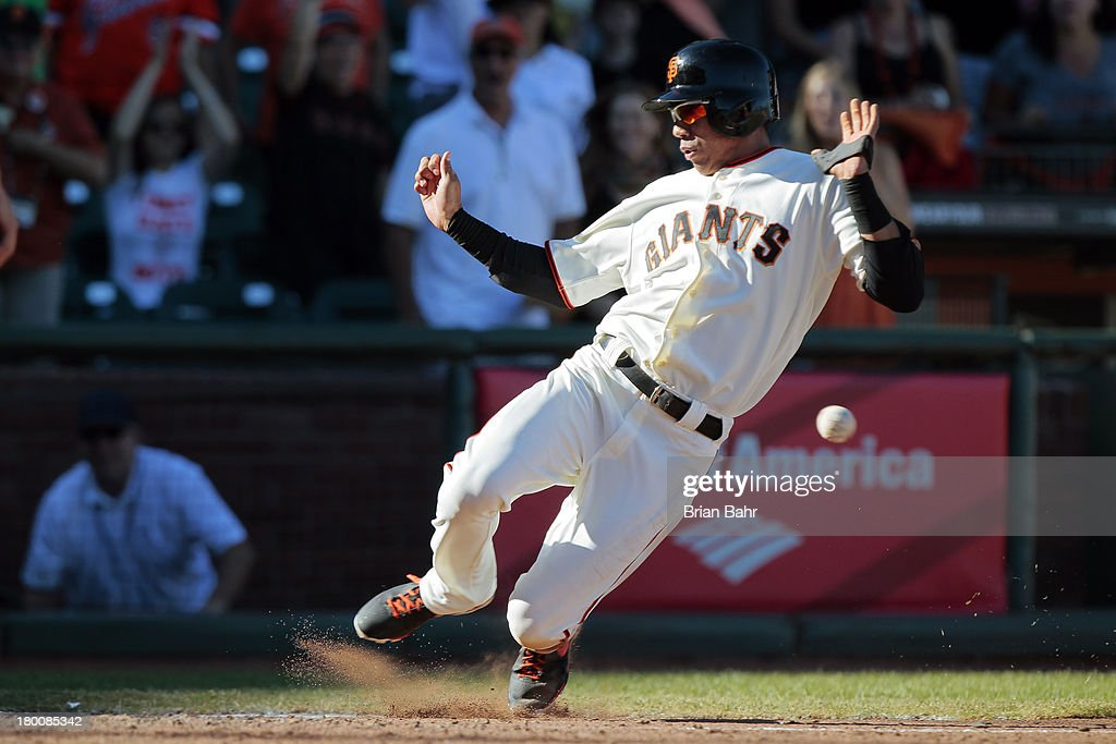 Ehire Adrianza #53 of the San Francisco Giants scores the winning run ahead of the tag on a walk-off single by Angel Pagan against the Arizona Diamondbacks in the 11th inning at AT&T Park on September 8, 2013 in San Francisco, California. The Giants won 3-2 in 11 innnings.