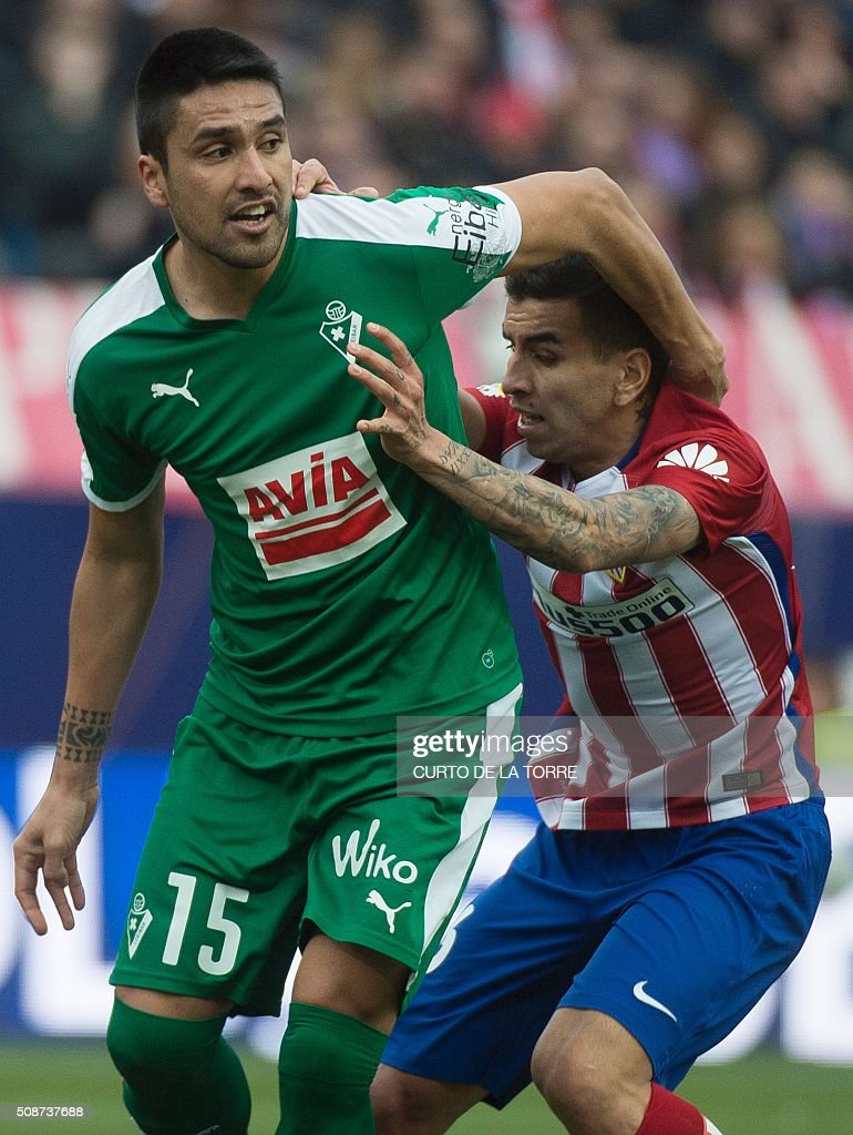 Eibar's Argentinian defender Mauro Dos Santos (L) vies with Atletico Madrid's Argentinian midfielder Angel Correa during the Spanish league football match Club Atletico de Madrid vs SD Eibar at the Vicente Calderon stadium in Madrid on February 6, 2016. AFP PHOTO / CURTO DE LA TORRE / AFP / CURTO DE LA TORRE