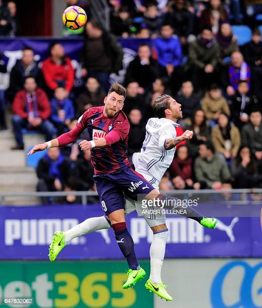 Eibar's forward Sergi Enrich vies with Real Madrid's defender Sergio Ramos during the Spanish league football match SD Eibar vs Real Madrid CF at the...