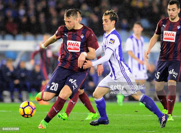 Eibar's French defender Florian Lejeune vies with Real Sociedad's forward Juanmi Jimenez during the Spanish league football match Real Sociedad vs SD...
