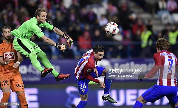Eibar's goalkeeper Yoel Rodriguez vies with Atletico Madrid's Uruguayan defender Jose Maria Gimenez and Atletico Madrid's French forward Antoine...