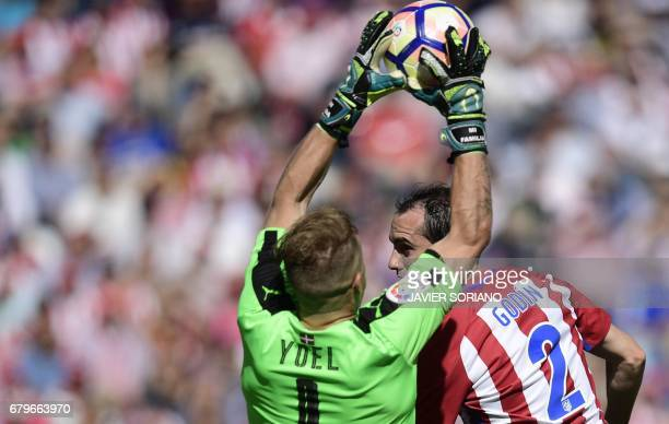 Eibar's goalkeeper Yoel Rodriguez vies with Atletico Madrid's Uruguayan defender Diego Godin during the Spanish league football match Club Atletico...