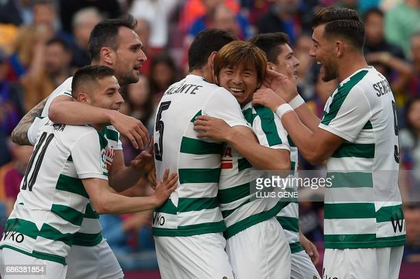 Eibar's Japanese midfielder Takashi Inui celebrates with teammates after scoring a goal during the Spanish league football match FC Barcelona vs SD...
