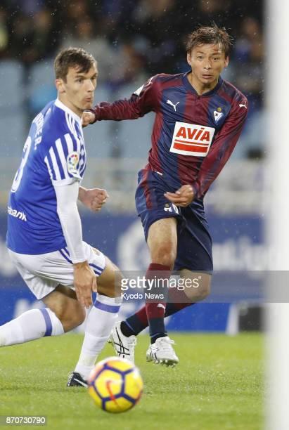 Eibar's Takashi Inui shoots past Diego Llorente of Real Sociedad in the first half of a Spanish La Liga match at Estadio de Anoeta in San Sebastian...