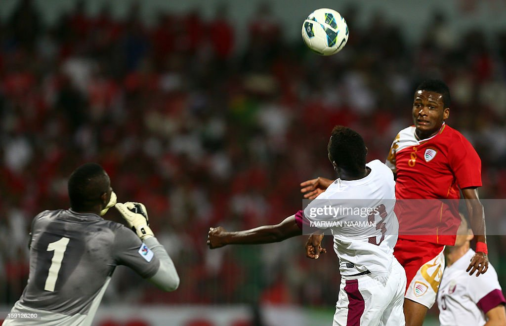 Eid al-Farsi (R) of Oman heads the ball towards the goal as Kasola Mohammed of Qatar (C) defends during their 21st Gulf Cup football match in Manama, on January 8, 2013.