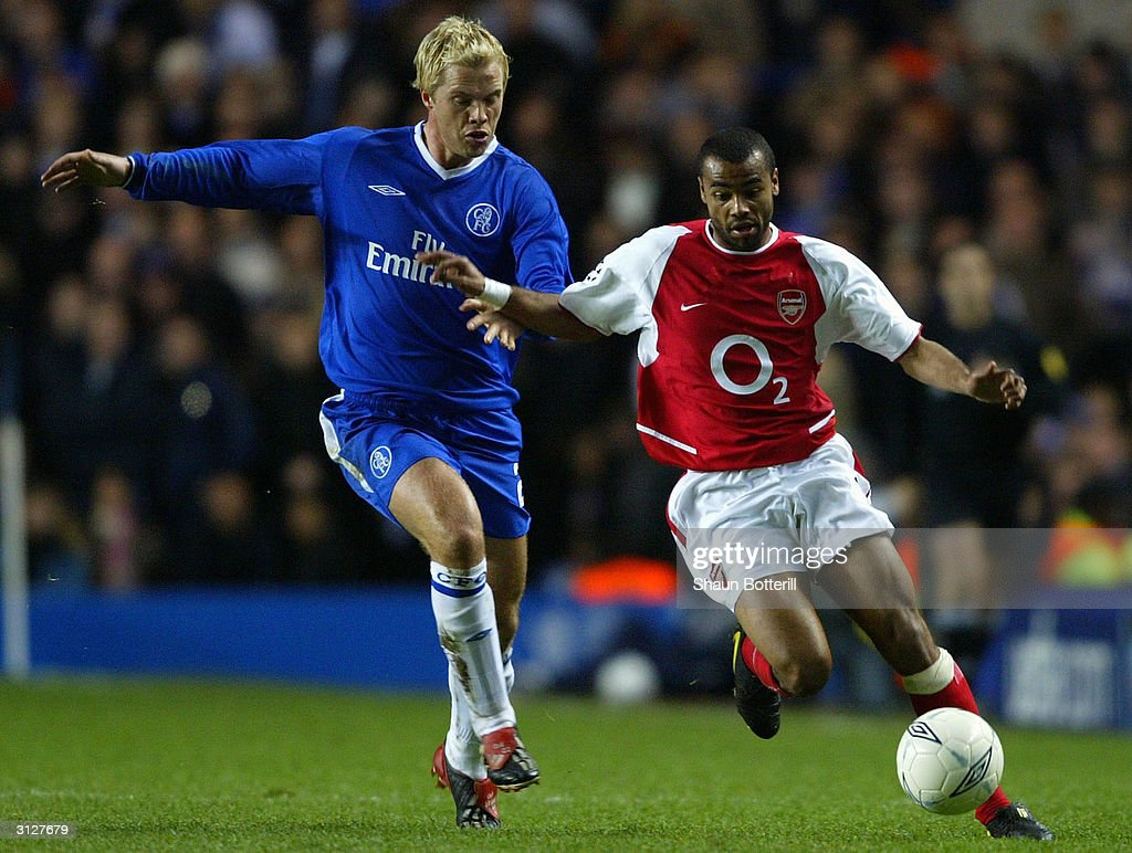 Eidur Gudjohnsen of Chelsea battles for the ball with Ashley Cole of Arsenal during the UEFA Champions League Quarter Final match between Chelsea and Arsenal at Stamford Bridge on March 24, 2004 in London.