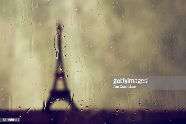 Eifel tower seen through a window on a rainy day - In studio
