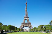Eiffel tower, sunny summer day with blue sky and green Field of Mars in Paris