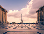 Eiffel tower, Paris symbol and iconic landmark in France, on a cloudy day. Famous touristic places and romantic travel destinations in Europe. Cityscape and tourism concept. Long exposure. Toned.