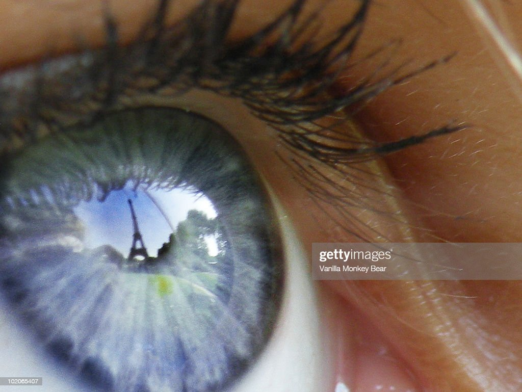 Eiffel Tower reflected in a girl's blue eye : Stock Photo