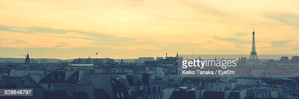 Eiffel Tower With Cityscape Against Orange Sky During Sunset
