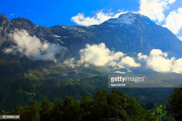 Eiger and Monch massif, above idyllic Grindelwald alpine valley and meadows, dramatic swiss snowcapped alps, idyllic countryside, Bernese Oberland,Swiss Alps, Switzerland