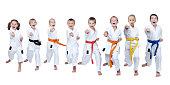Eight athletes in karategi hit punch arm