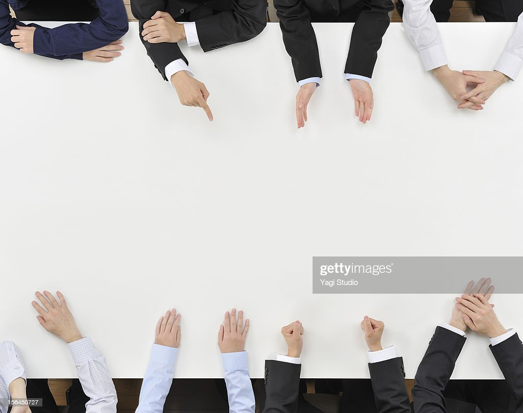 Eight business people having discussion on desk : Stock Photo
