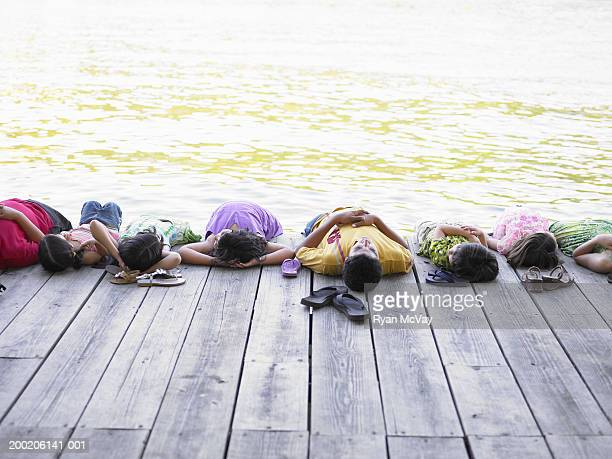 Eight children (3-12) lying side by side on dock