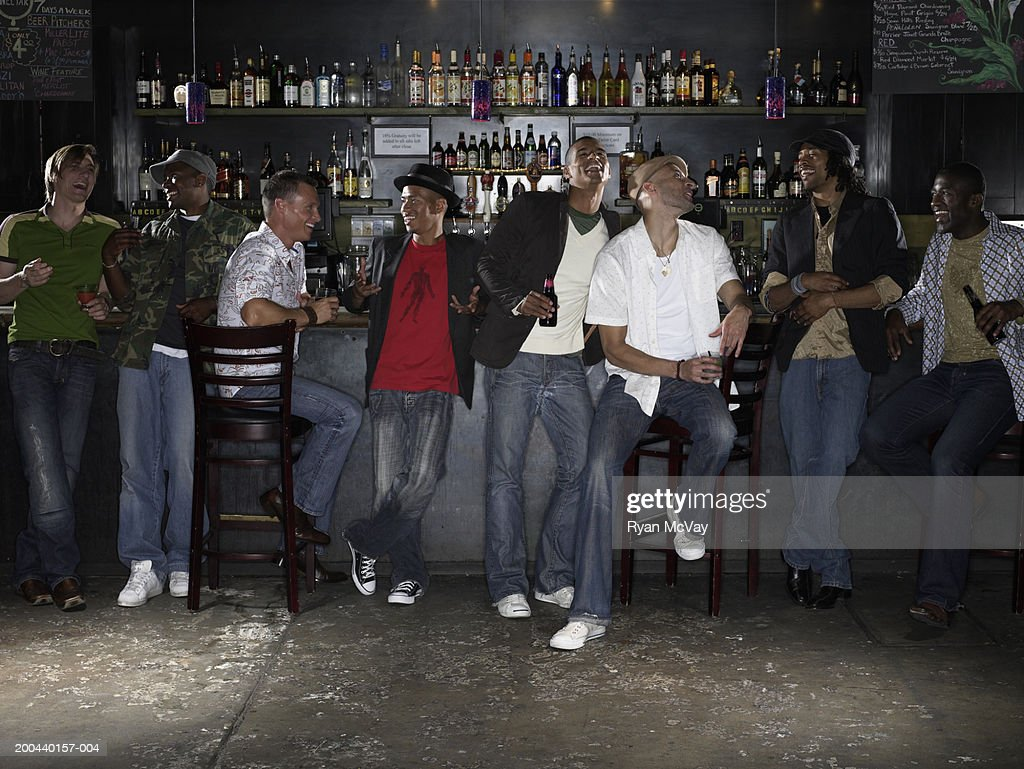 Eight men drinking alcohol and laughing in bar