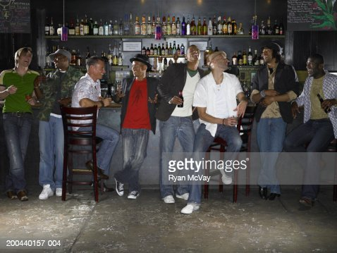 Eight men drinking alcohol and laughing in bar : Stock Photo