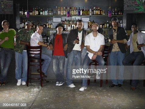 Eight men side by side in bar, portrait : Stock Photo