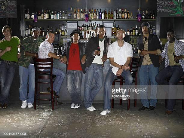 Eight men side by side in bar, portrait