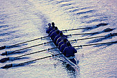 Eight men sweep rowing; coxswain in front of boat